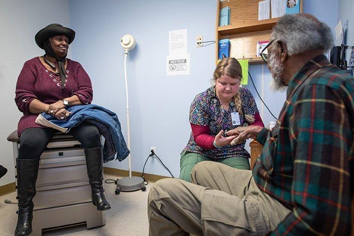 Nurse assistant checks vitals on a senior citizen.